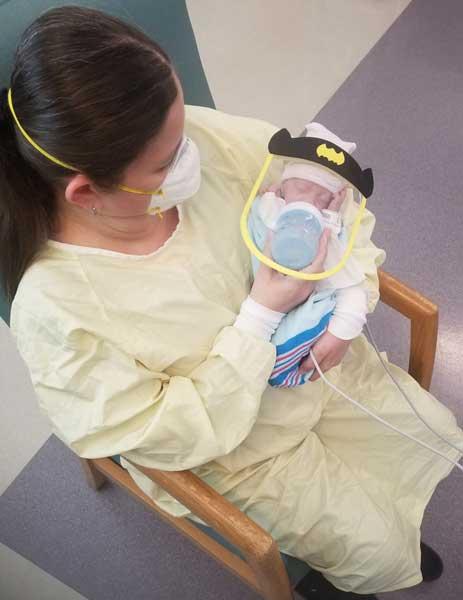 Miembro del personal que alimenta al bebé con careta