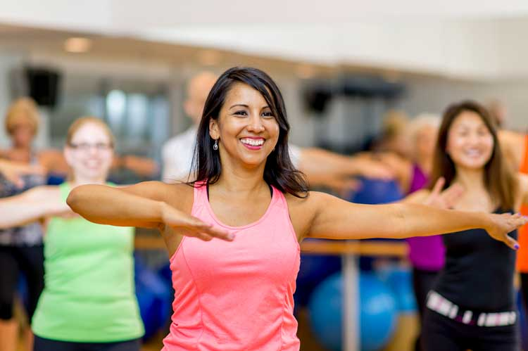 Woman smiling in group dance fitness class