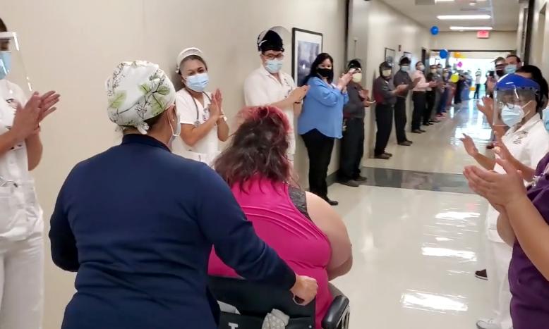 Los trabajadores del hospital se alinean en los pasillos para celebrar el alta de la paciente recuperada de COVID-19 Nora D. Martínez.