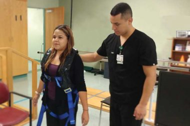 Patient using unique harness system with healthcare provider standing nearby