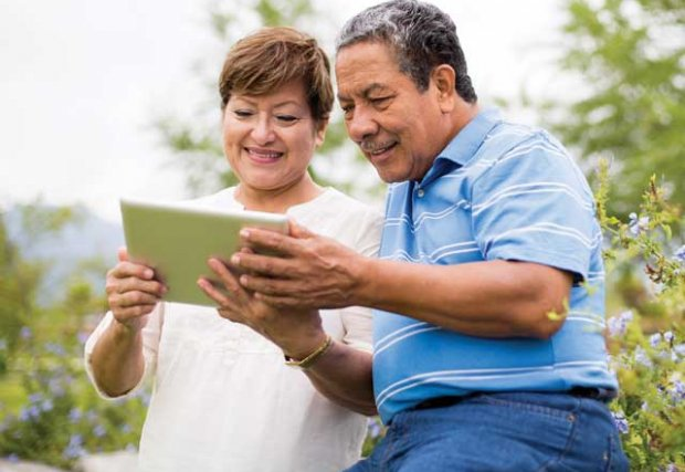 Older couple looking at an ipad in outdoor setting