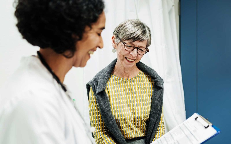smiling patient and doctor looking at a chart together